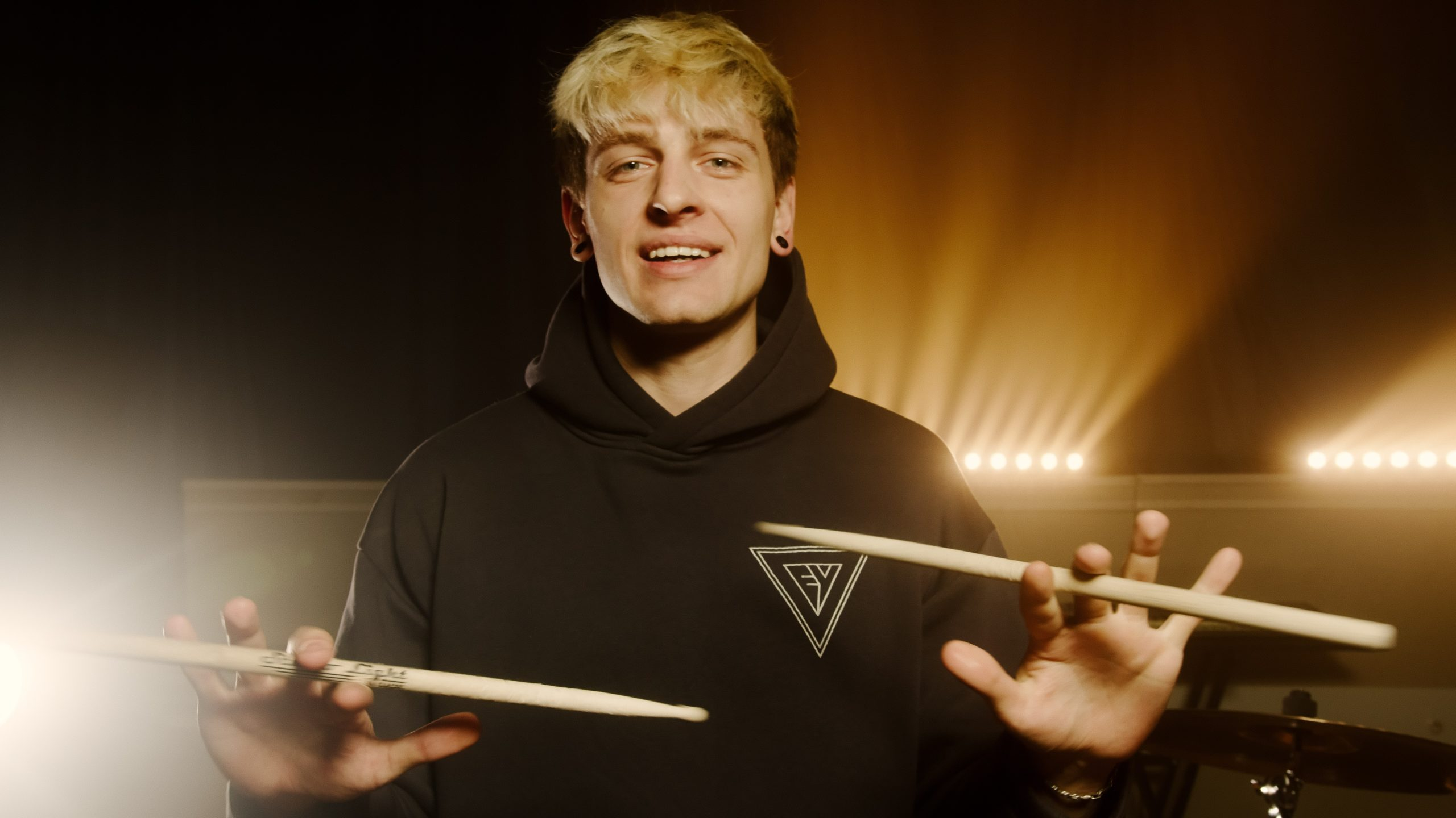 Happy Drummer spinning his sticks in his fingers. To demonstrate how drums improves mental health